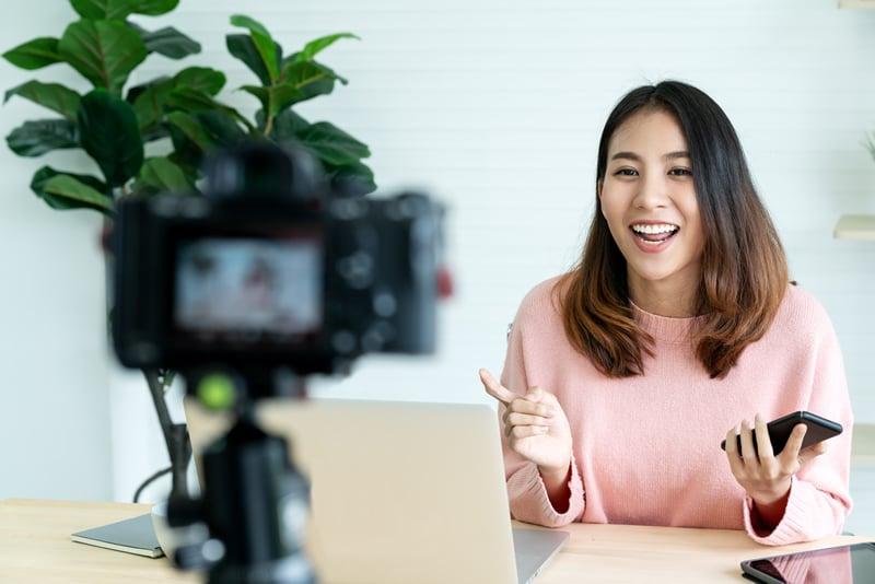 Mujer con cabellos suelto grabando un videoblog