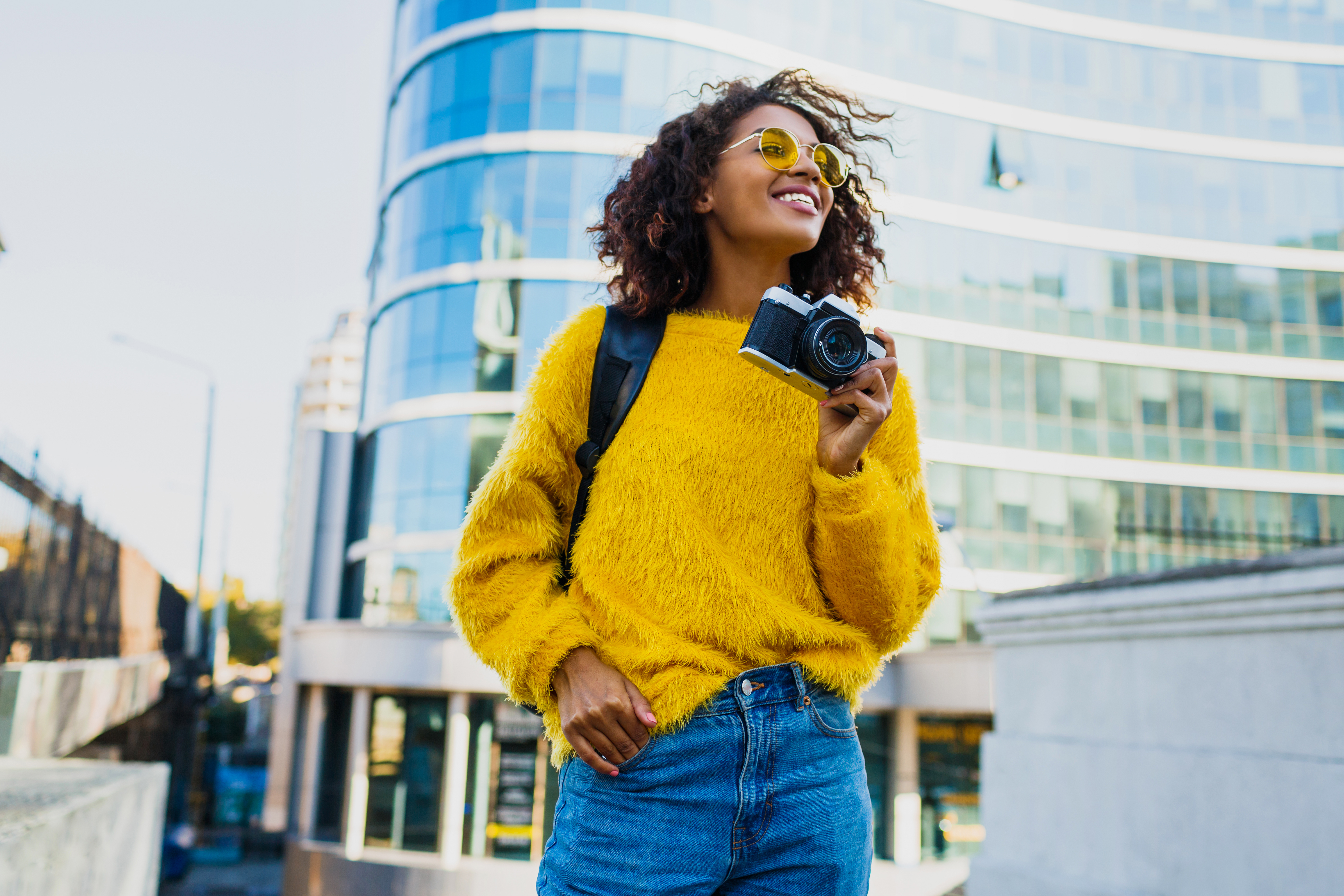 happy-confident-african-woman-holding-photo-camera-WMQZHUD