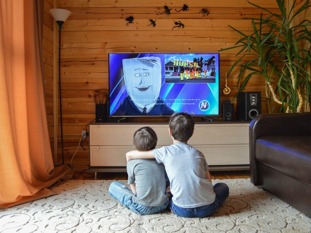 Crianças sentadas no tapete da sala assistindo Smart TV