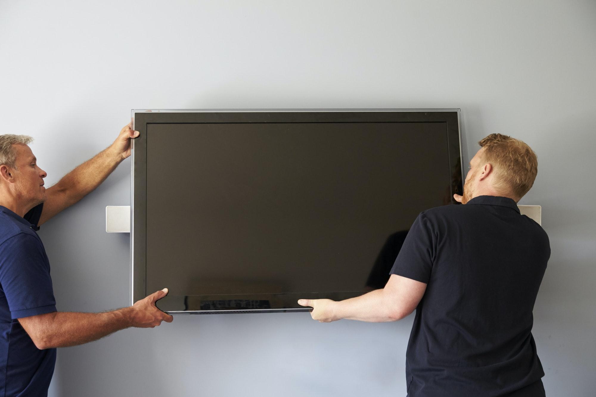 Dois homens instalando TV